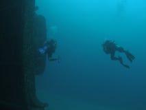 Scuba-duikers en een schipwrak stock foto's