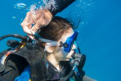 Scuba instructor opened the air valve on wetsuit for immerse Royalty Free Stock Photos