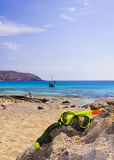 Scuba mask and snorkel on the rock with blue sea in background Stock Images