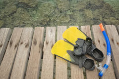 Scuba mask with yellow flippers. On wooden pier background Royalty Free Stock Photo