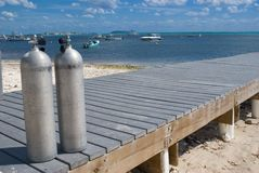 Scuba Tanks. On dock ready for divers in Grand Cayman. Dive boats in Background Stock Photos