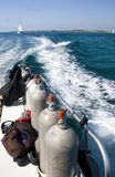Scuba Tanks & Wake. View of scuba tanks and boat wake with sailboat in the distance Royalty Free Stock Photos