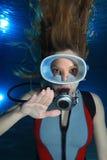 Scuba woman. Female scuba diver make hand signal slow down Royalty Free Stock Photo