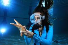 Scuba woman wand sea star stock photo