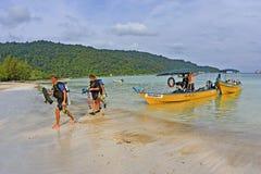 Scubadykare som går på strand efter en dyk, snubblar royaltyfri foto
