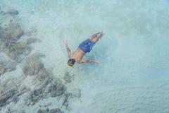 Scubra asiático do homem que conduz para ver o coral sob o mar na ilha de KohKham fotos de stock royalty free