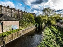 Scudding Clouds over Water of Leith, Early Spring, Edinburgh, Scotland. The bright light and shadow of early spring illuminates the Water of Leith as it flows Royalty Free Stock Photo