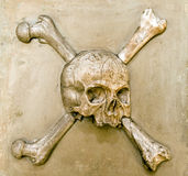 Scull and bones. Marble relief of scull and bones on a tombstone stock photos