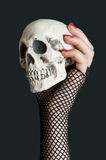 Scull in the hand on black background. Scull in the hand with red nails on black background royalty free stock image