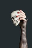 Scull in the hand on black background. Scull in the hand with red nails on black background royalty free stock photography