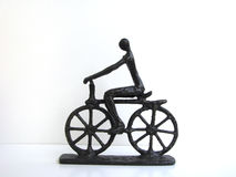 Sculpted Cyclist. Bronze metal sculpture of a rider pedaling a bicycle against a stark white background Stock Photography