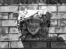 Sculpted Face. A shot of a sculptured face hung on a brick wall Royalty Free Stock Photos