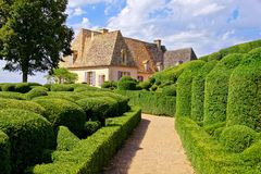 Sculpted gardens with historic house, Dordogne, France. Beautiful sculpted gardens with traditional house, Dordogne, France Stock Images