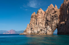 Sculpted red rock with a gap in the Gulf of Porto Royalty Free Stock Images