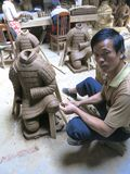 Sculpter Sculpts a Large Replica Terracota Warrior in Xian. XI'AN, CHINA - OCT. 2013: A Chinese sculpter in Xi'an scults a replica terra cotta warrior in a Royalty Free Stock Image