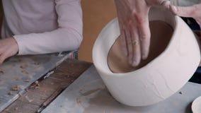 Sculpteur adulte avec la fille faisant la poterie de métier dans de petits travaux banque de vidéos