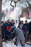 Sculpteur Chainsaw de glace et foule au carnaval d'hiver Photos stock