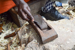 Sculpteur kenyan affilant un burin Photos libres de droits