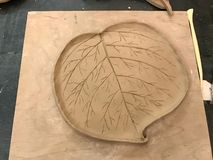 Sculpting clay in the process. Preparation of a clay flat plate in the form of a leaf on wooden board. Top view royalty free stock photography