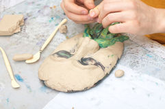 Sculpting. Hands sculpting plasticine form of face with moustache Stock Photography