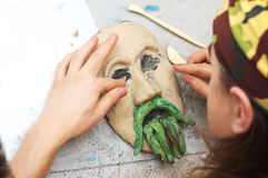 Sculpting plasticine form of face with moustache Royalty Free Stock Photo