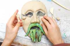 Sculpting plasticine form. Man hands sculpting plasticine form of face with moustache Stock Photography