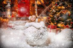 Sculpting snowman in yard. Pretty child girl sculpts a snowman near her house decorated for Christmas. Merry Christmas and Happy New Year royalty free stock photos