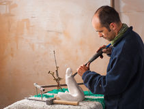 Sculptor. Working on his art at his workshop Royalty Free Stock Photo