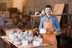 Sculptor in atelier with teapot. Sculptor man standing in atelier and holding white clay teapot Royalty Free Stock Photo