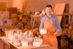 Sculptor in atelier with teapot. Sculptor man standing in atelier and holding white clay teapot Stock Photo