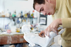 Sculptor carefully attach legs to statuette. Sculptor carefully attach legs to plaster statuette and critically examine result Stock Photos