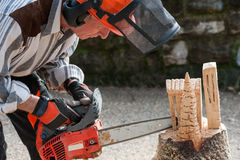 The sculptor carves the wood with the chainsaw. During a public demonstration Royalty Free Stock Photography