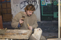 Sculptor carving a sculpture of a woman in a woode Royalty Free Stock Images