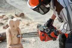 The sculptor with the chainsaw. The sculptor carves the wood with the chainsaw stock photo