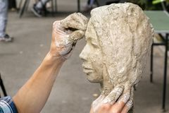 Sculptor creates a bust and puts his hands clay on the skeleton of the sculpture. Close-up royalty free stock photography