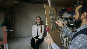 Sculptor creating sculpture of human`s face on canvas while young woman posing him in art studio. Indoors stock video