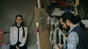 Sculptor creating sculpture of human`s face on canvas while young woman posing to him in art studio. Indoors stock video