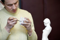 Sculptor files attentively fragment of sculpture. Sculptor files attentively in the studio a fragment of the plaster sculpture royalty free stock photo