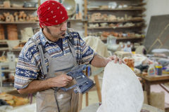 Sculptor grinds stone Stock Photo