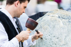 Sculptor with mallet and cutter working on erratic block Royalty Free Stock Photo