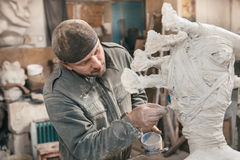 Sculptor man working in his workshop Royalty Free Stock Photos