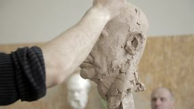Sculptor modelling sculpture adjusting face details head made of clay. stock footage