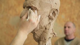 Sculptor modelling sculpture adjusting face details head made of clay. stock video