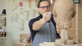 Sculptor modelling sculpture adjusting face details head made of clay. Creative concept stock footage