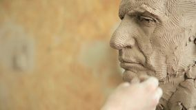 Sculptor modelling sculpture adjusting face details head made of clay. stock video footage