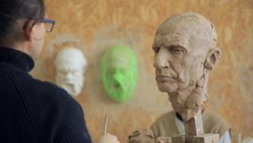 Sculptor modelling sculpture adjusting face details head made of clay. Creative concept stock video