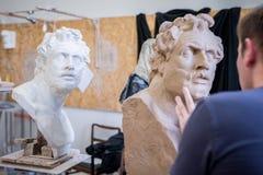 A sculptor sculpts a sculpture of a person`s face. Horizontal frame stock photos