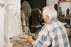 Sculptor standing at his new work Royalty Free Stock Photo