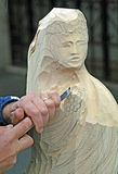 Sculptor who carves a statue. Sculptor who carves a wooden statue Stock Image