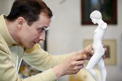 Sculptor works with concentration in studio Royalty Free Stock Images